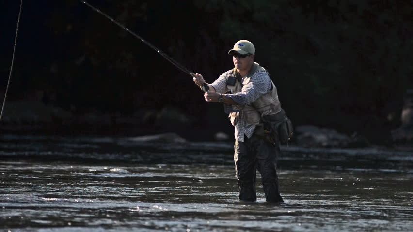 A man in waterproof overalls stands in a river and casts his lure with his rod while he spends his day fly fishing.