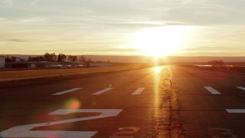 A small airplane flies over and lands in a brilliant sunset. - HD stock video clip