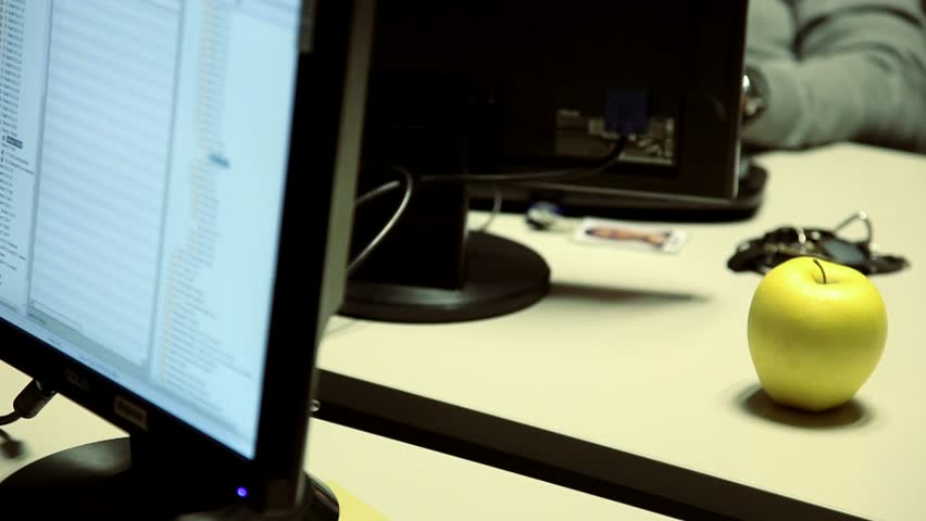 Man taking an apple while working on his desk. Time for break and healthy lunch. - HD stock video clip