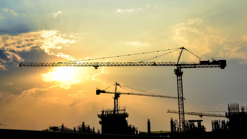 time lapse sunset and silhouette crane working in construction site