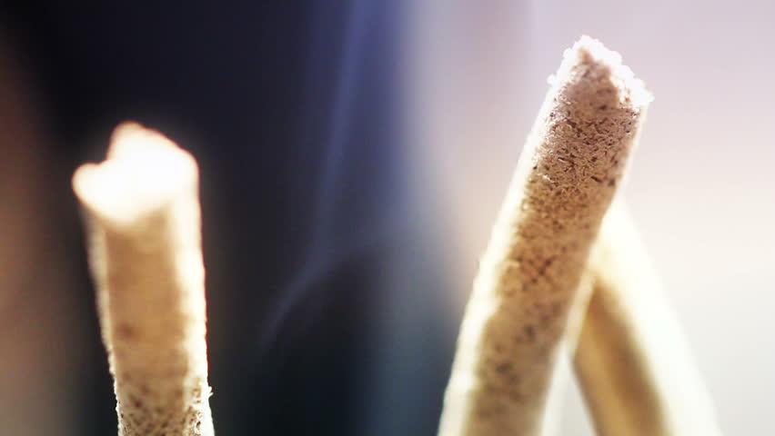 Close up of burning incense sticks with smoke over black background