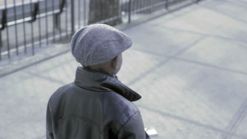 Young African American Kid walking down the street with a black coat and hat - HD stock footage clip