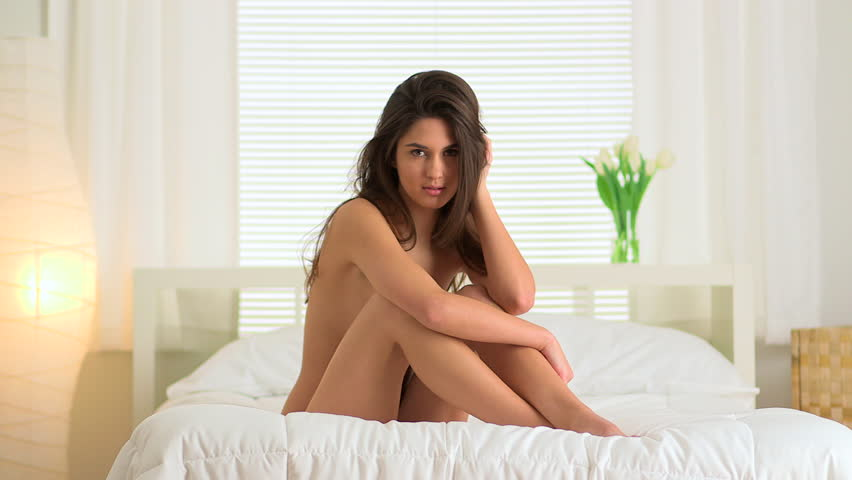 Nude woman playing with hair on bed - HD stock footage clip