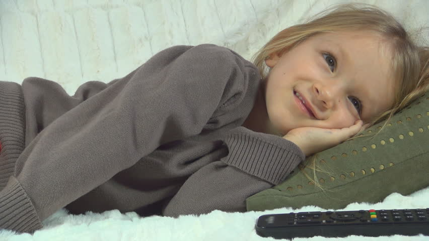 Child Smiling Watching TV, Sleepy Little Girl Lying on the Couch, Sofa, Children - HD stock footage clip