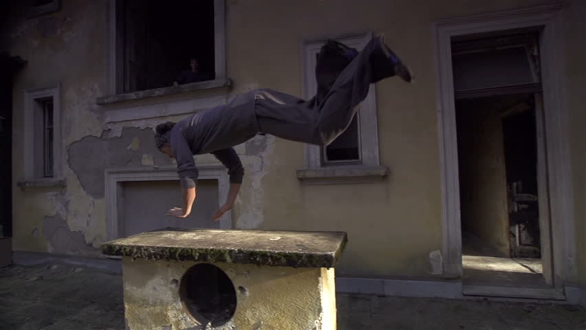 SLOW MOTION: Free runners jumping over a stone obstacle