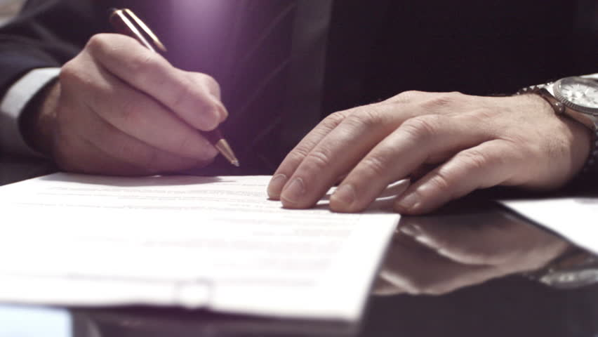 Businessman sitting at shiny office desk signing a contract with noble pen