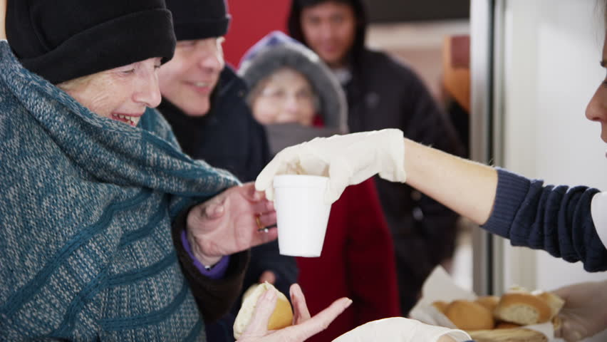Friendly voluntary workers standing at a soup kitchen serving hatch are handing out cups of hot soup and bread to a waiting line of homeless and needy people. - HD stock video clip