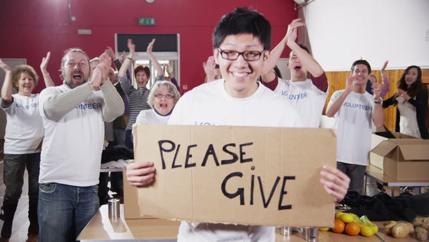 """A male charity volunteer of Asian ethnicity holds up a """"Please Give"""" sign and smiles at the camera as his fellow volunteers applaud and cheer in the background. In slow motion. - HD stock video clip"""
