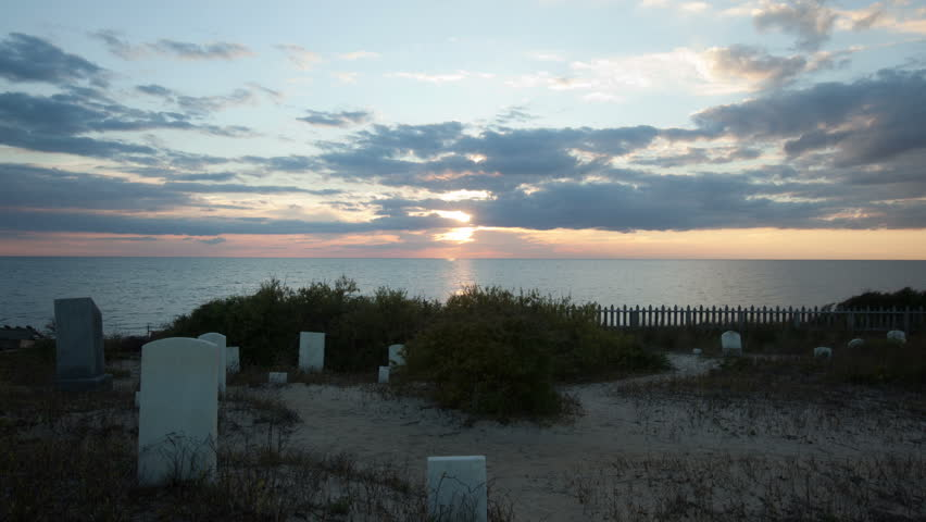 Sunset time-lapse at Graveyard near water with tombstones