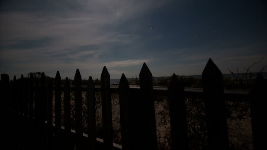 Graveyard night sky time-lapse moving along fence with tombstones