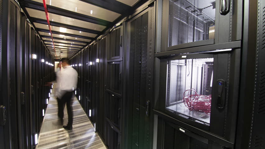 Group of  IT engineers of mixed ethnicity carry out an inspection and maintenance procedure on servers in a dark data center. In time lapse