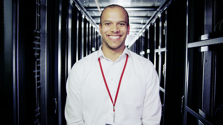 Portrait of a male IT engineer who is working in a data center with rows of server racks and computers.