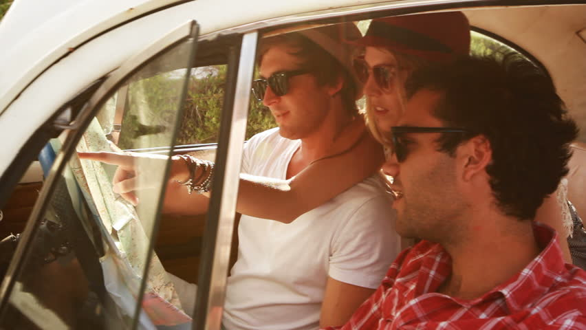 Young Hipster friends on a roadtrip looking at a map. - HD stock footage clip