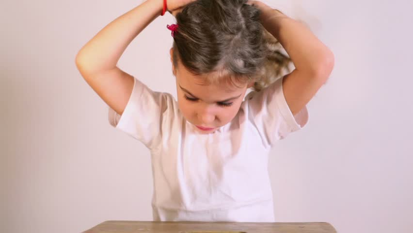 Little girl in white shirt sits at table and ties her hair with rubber bend - HD stock footage clip