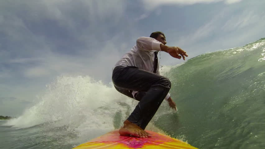 Cheerful businessman on surf board rides a tropical ocean wave | Shutterstock HD Video #3631229