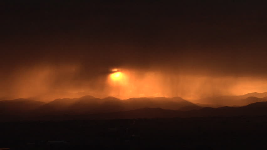 Sunset in the Rain. Sun sets behind sheets of falling rain - HD stock footage clip