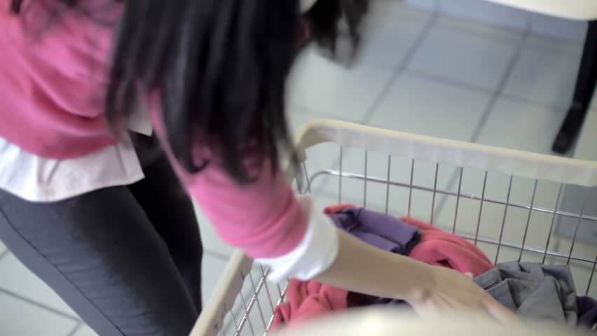 Woman putting clothes in the washing machine