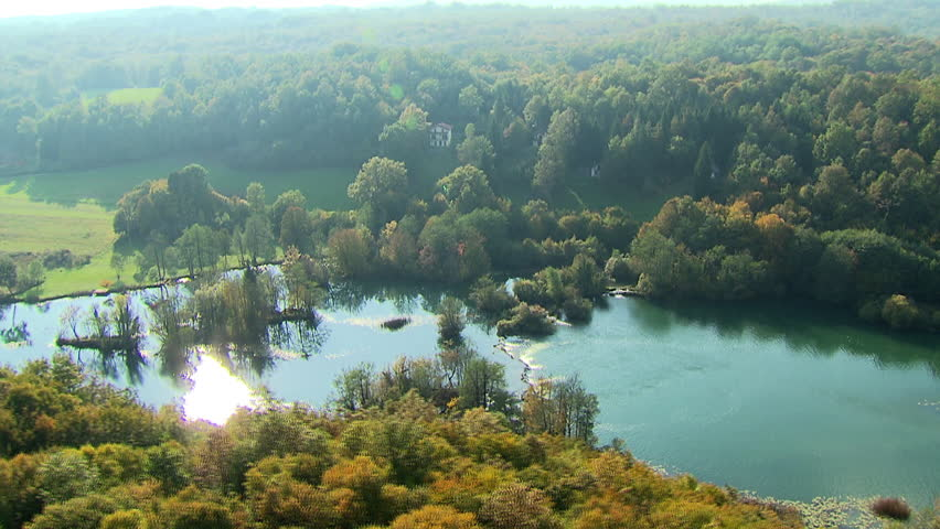 Helicopter flying over a scenic river surrounded by beautiful nature. Aerial