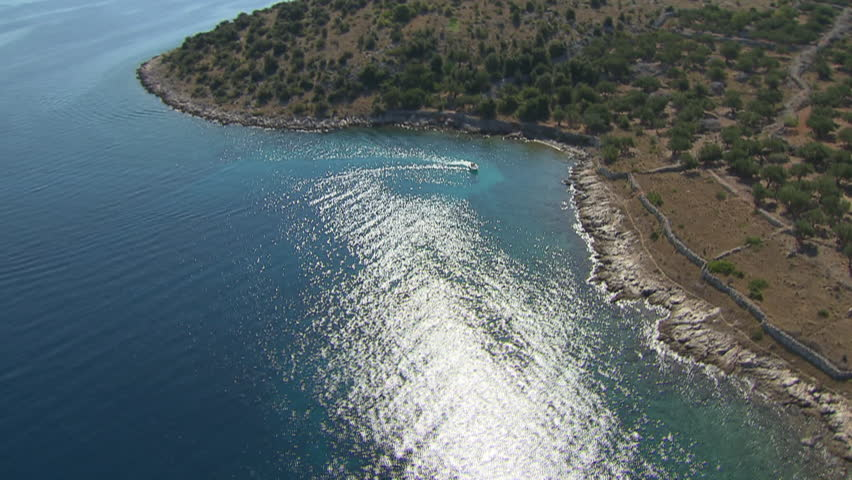A desolate beach belonging to Kornati archipelago, calm sea and a boat. Aerial helicopter shot.