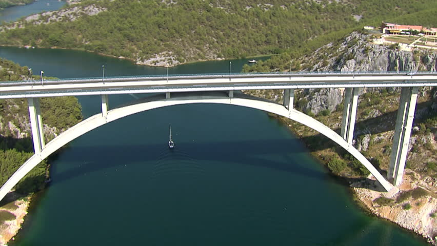 Zooming-in to a car driving across the Krka bridge then zooming-out to whole
