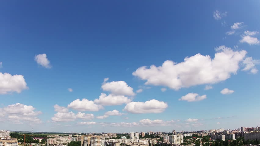Summer. Sunshine and blue sky. The small city. Clouds and shadows of clouds are