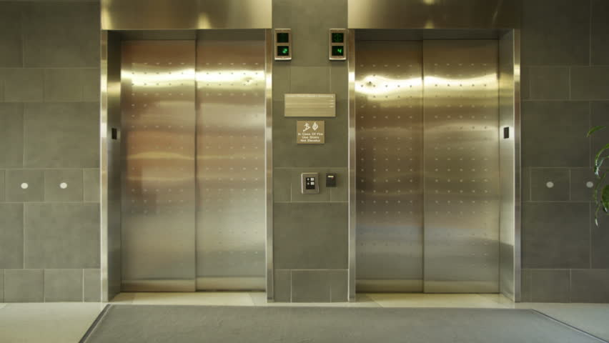 Empty elevator arrives, doors open and close. Wide, locked off shot.