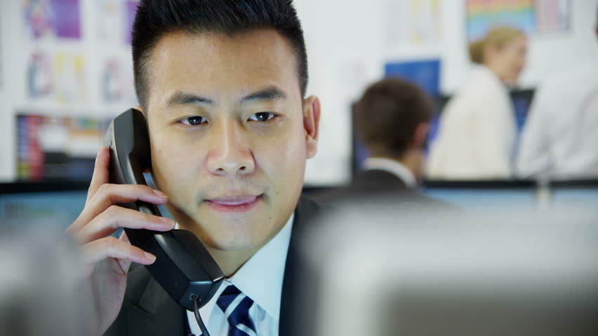 Young and ambitious stock market trader is doing a deal over the phone in a busy office filled with computers. The rest of his team are hard at work in the background.  - HD stock video clip