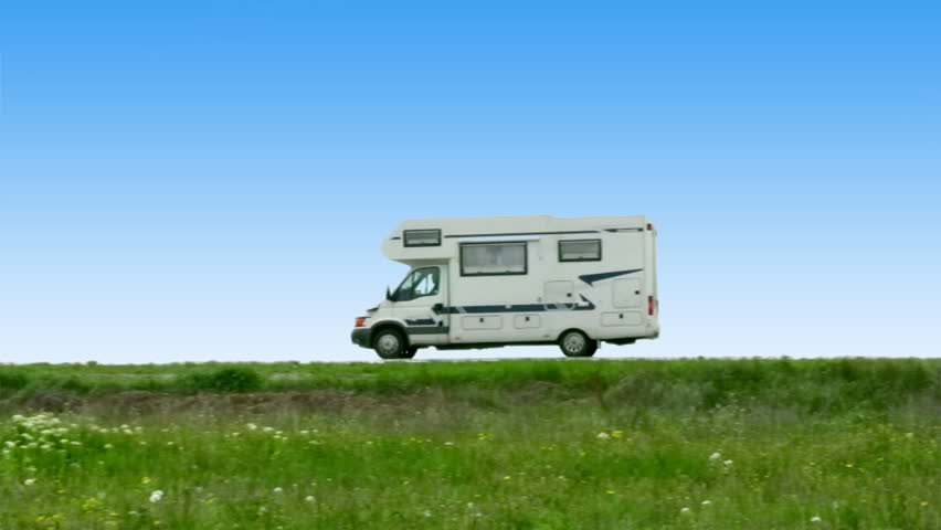 The camper leaves on road on a background of steppe grasses and the blue sky