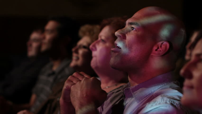 Young man has various reactions while watching a movie with a group of friends. Ends with everyone clapping. Focus on him with a small dolly move and projections on his face.