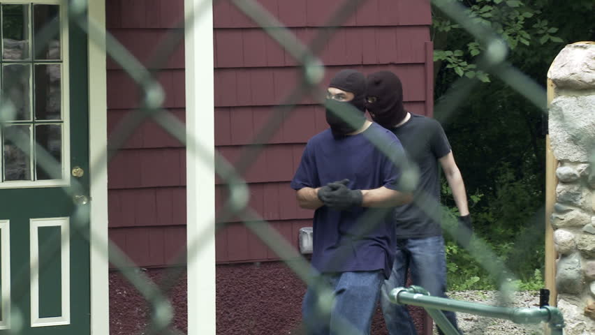 Two masked burglars make their way through an open gate and get into a house