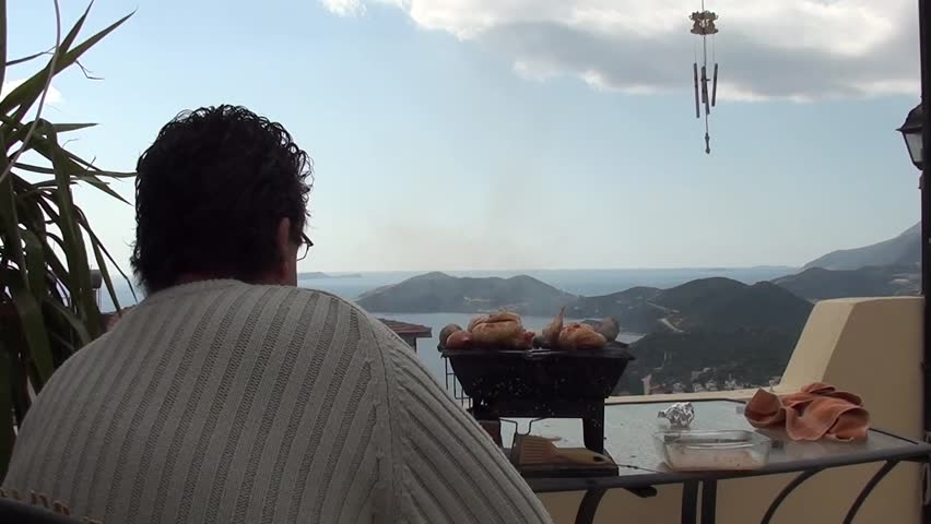 A man watching chicken on grill, beautiful view in the background