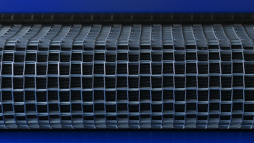 View from the front of a steel mesh conveyor belt operating, then stopping and