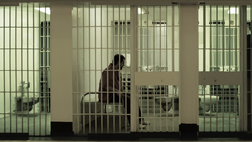 Inmate gets up from bed to stand at the bars of his prison cell. Neighboring inmate can also be seen pacing. Desaturated color.