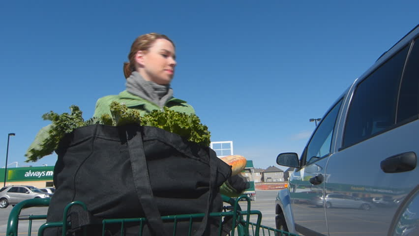 Young Woman Pushing A Supermarket Shopping Cart Full Of Groceries Back To Her Vehicle