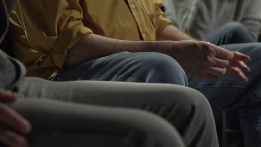 Man giving his testimony at a support group, crying