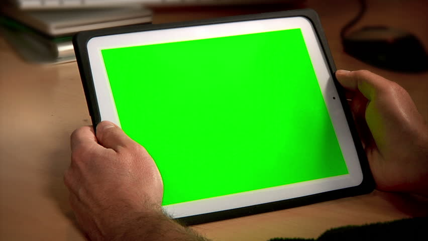 A man uses a tablet PC at his desk.  Chroma key screen for placement of your own