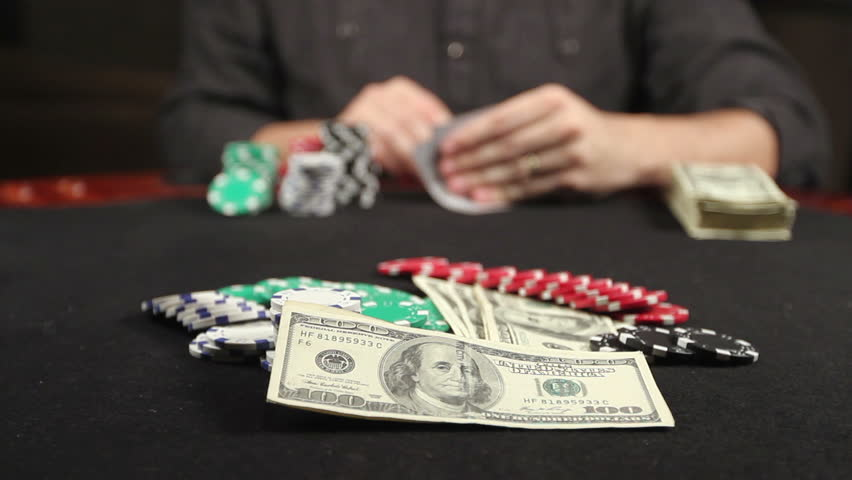 A gambler at a poker table peeks at his cards and bets a stack of chips - HD stock video clip