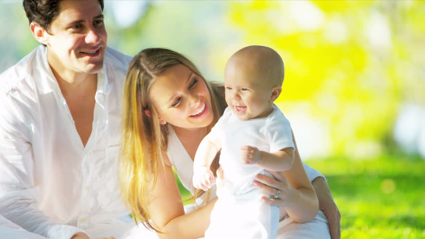 Close up smiling Caucasian parents sitting on grass in park holding up their cute young baby son shot on RED EPIC