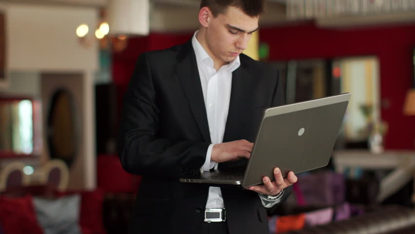 Guy standing in cafe with laptop and typing