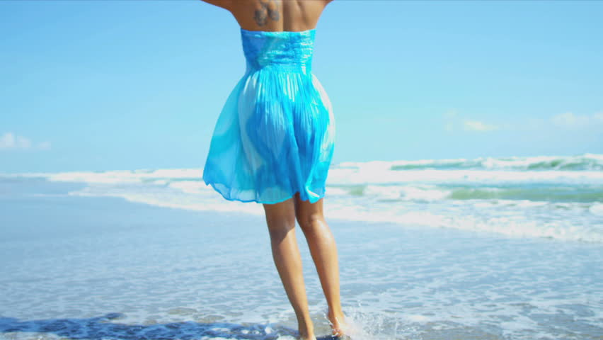 Bare legs feet young African American girl walking on wet sand beside ocean shot on RED EPIC