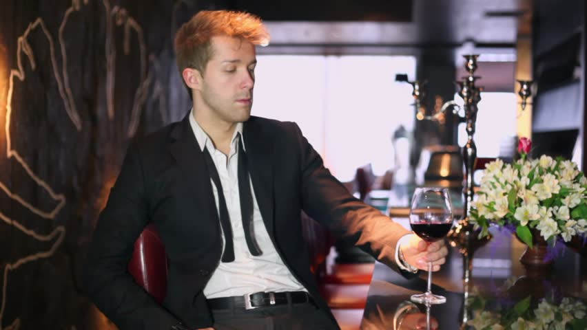 Blond man in black suit drinks wine during sits in bar - HD stock footage clip