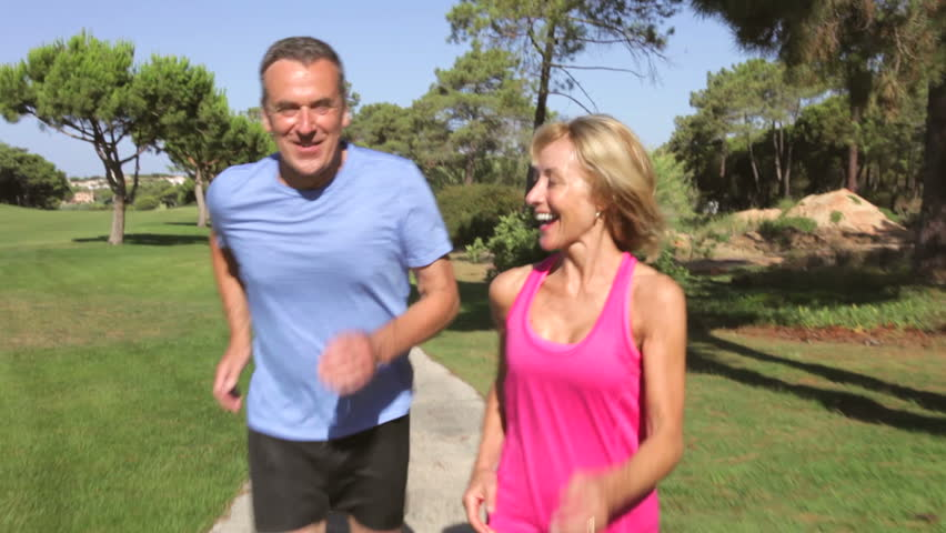 Senior couple in park jogging towards and then past camera position. Shot on Canon 5d Mk2 with a frame rate of 30fps #3789998
