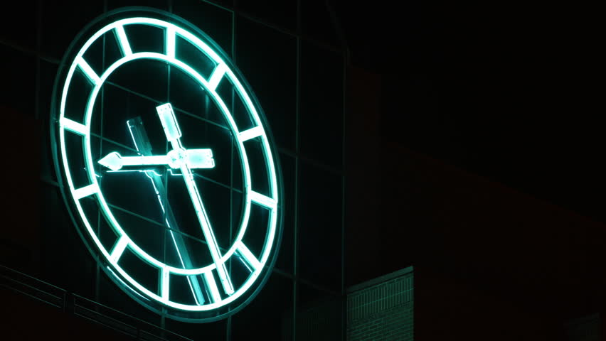 Huge neon clock on a building, at night. HD 1080p timelapse.