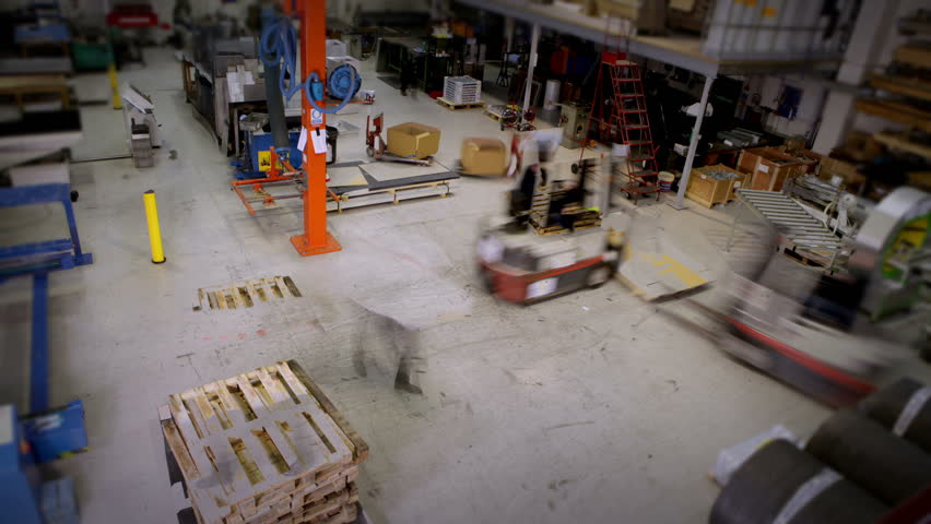 Time-lapse clip of busy workers in a warehouse or factory, wearing high visibility clothing and hard hats. They are checking stock levels and using a forklift truck to move empty wooden pallets. - HD stock footage clip