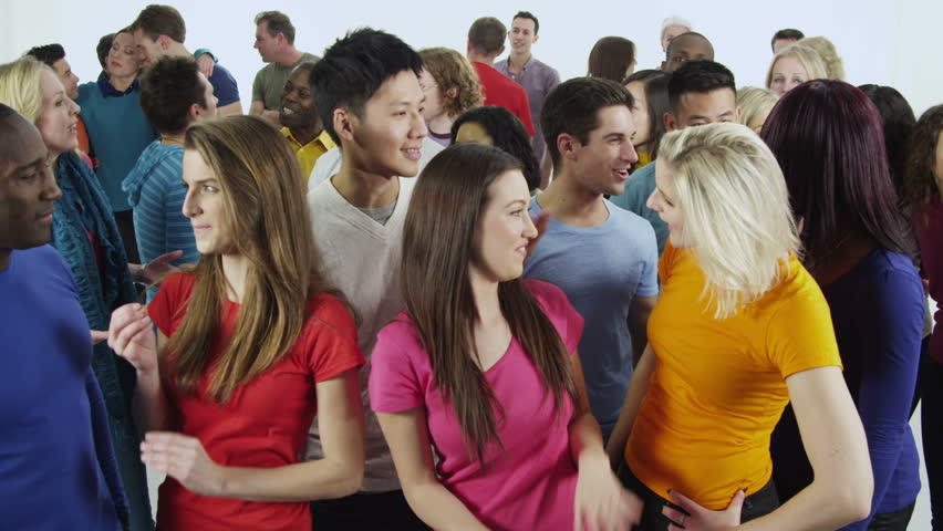 Portrait of a happy and diverse multi ethnic group of people who are standing together, in brightly colored casual clothing and having fun. They are isolated on white in a studio shot.  In slow motion