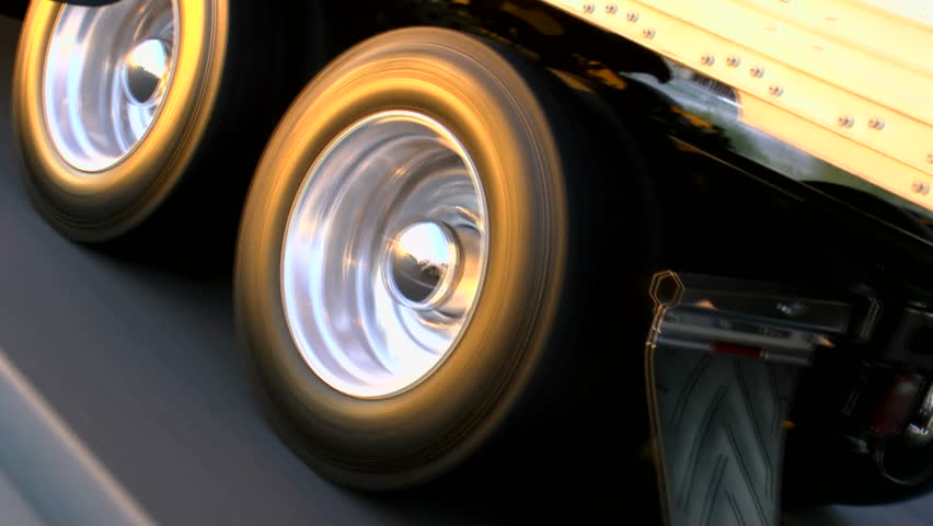 Truck tire wheels spin, close up, glow in late afternoon sun as rig rides smooth, open highway. 1080p | Shutterstock HD Video #3817133