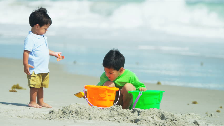 Young Hispanic children playing together on sandy beach shot on RED EPIC - HD stock video clip