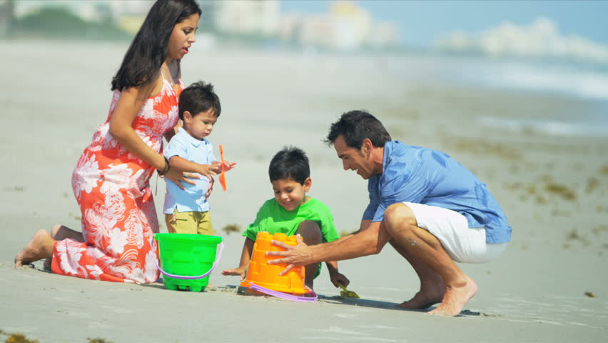 Young Latin American boys building sand castles with loving parents on beach shot on RED EPIC - HD stock footage clip