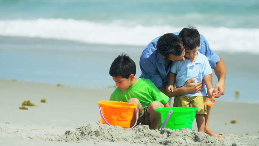 Happy Hispanic father helping sons with sand castles on beach shot on RED EPIC - HD stock footage clip