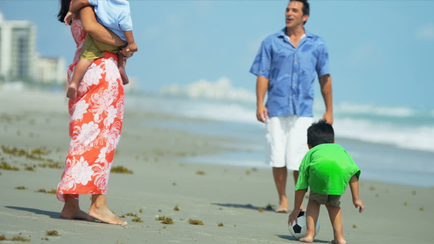 Happy Latin American family enjoying leisure time with young sons on beach playing football shot on RED EPIC - HD stock video clip